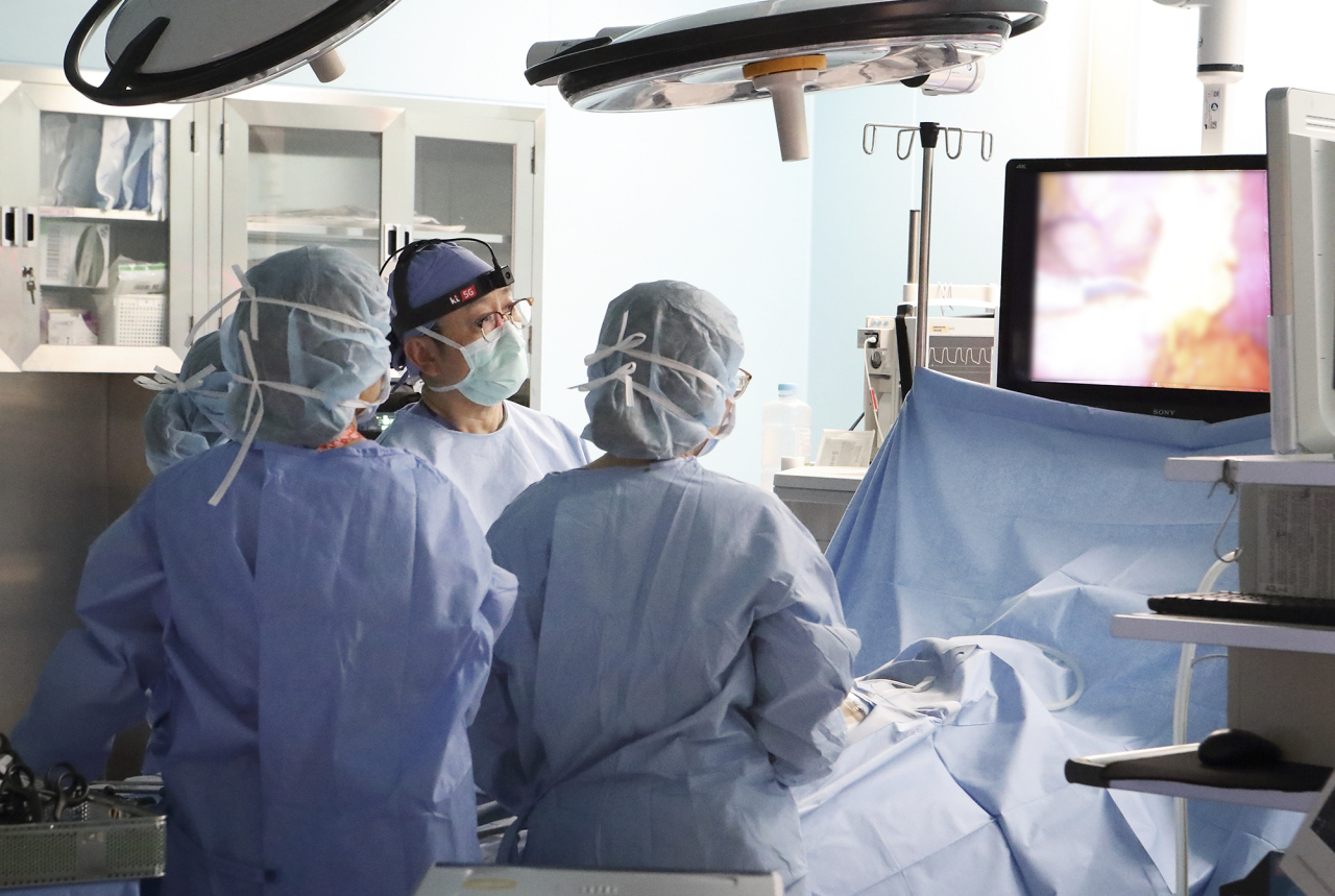 Medical personnel at the Samsung Medical Center observe surgery in an operating room, via a screen that shows real-time images from the surgeon's wearable device, thanks to a 5G network-enabled system. (KT)