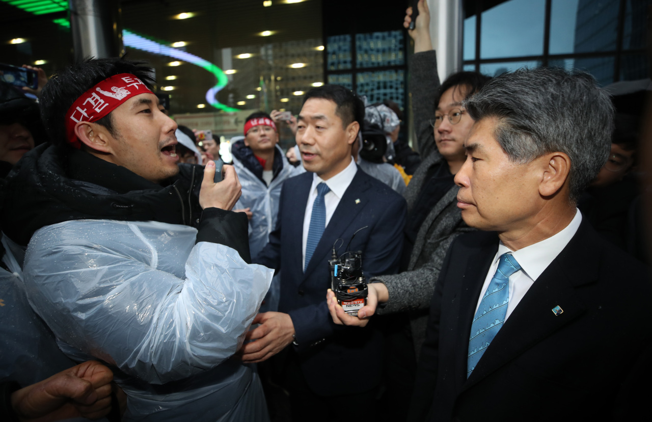 IBK CEO Yoon Jong-won is blocked by a union member outside the bank's headquarters in central Seoul on Jan. 7. (Yonhap)