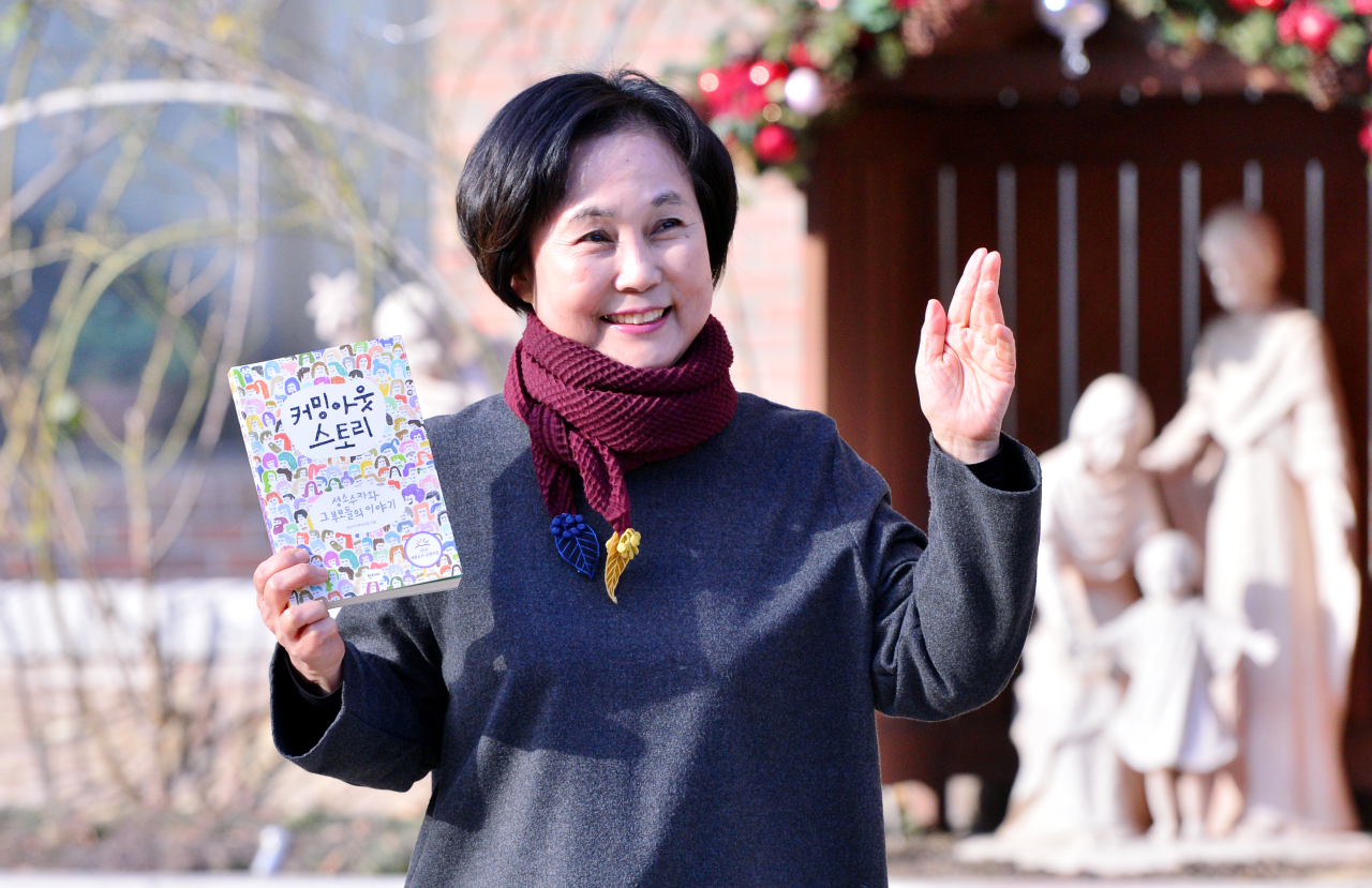 "Hong Jung-seun poses for a photo on Jan. 16 in front of a Catholic church in southwestern Seoul while holding a book, titled ""Coming Out Story,"" which she co-authored with other parents of LGBT people. (Park Hyun-koo/The Korea Herald)"