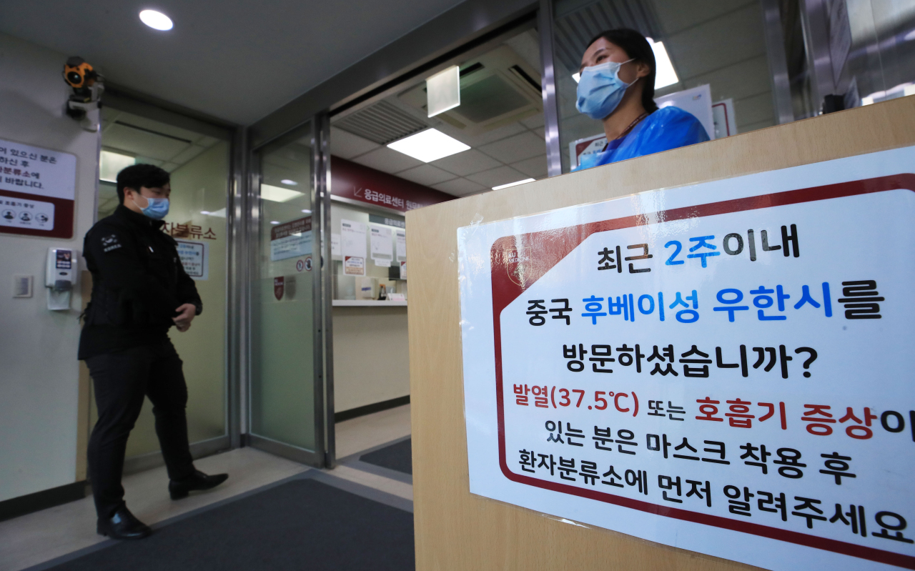 A notice with instructions for people displaying symptoms with a history of visiting Wuhan within the past two weeks is seen at an emergency room at a hospital in Seoul on Wednesday. Yonhap