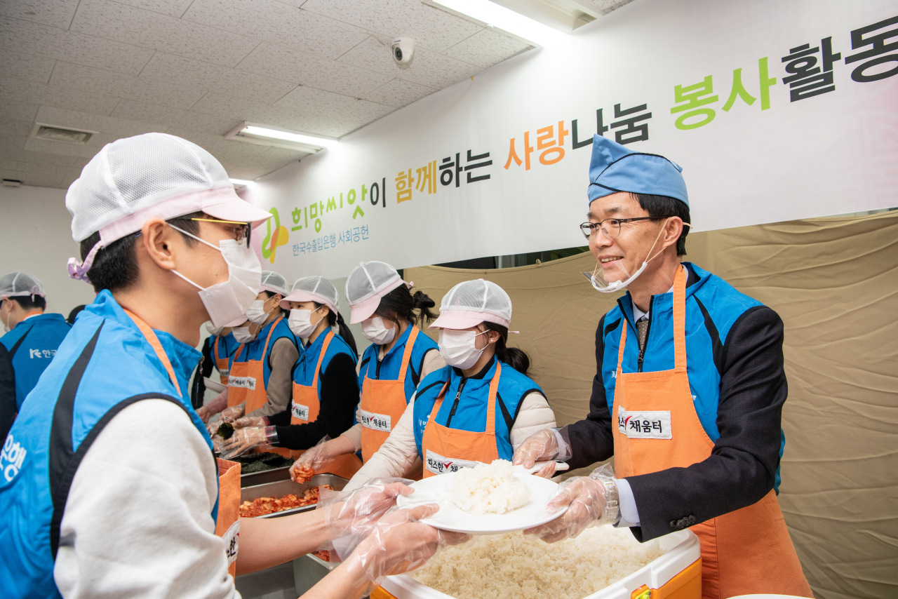 Eximbank CEO Bang Moon-kyu (right) serves food along with employees at the Warm Hearted Food Supply Center near Seoul Station on Tuesday. (Eximbank)