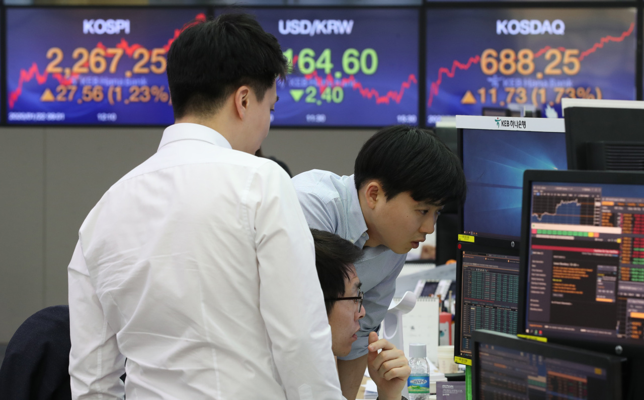 Traders watch monitors at the foreign exchange dealing room of the KEB Hana Bank headquarters in Seoul on Wednesday. (Yonhap)