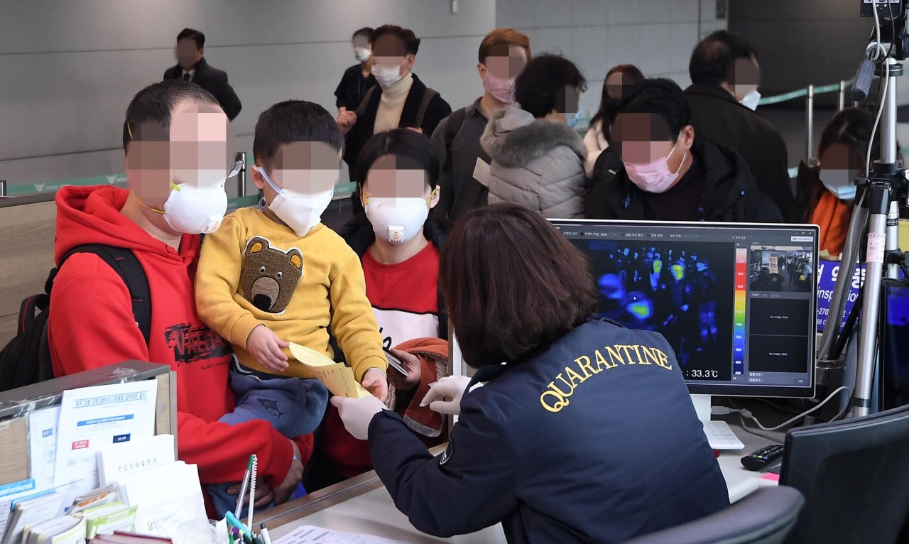Passengers arriving from China are scanned by a thermal sensor at Incheon Airport on Tuesday. (Yonhap)