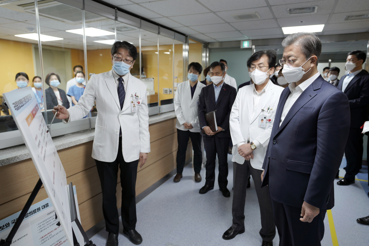 President Moon Jae-in is briefed by National Medical Center officials on the measures for the coronavirus outbreak at the National Medical Center in Seoul on Tuesday. Yonhap