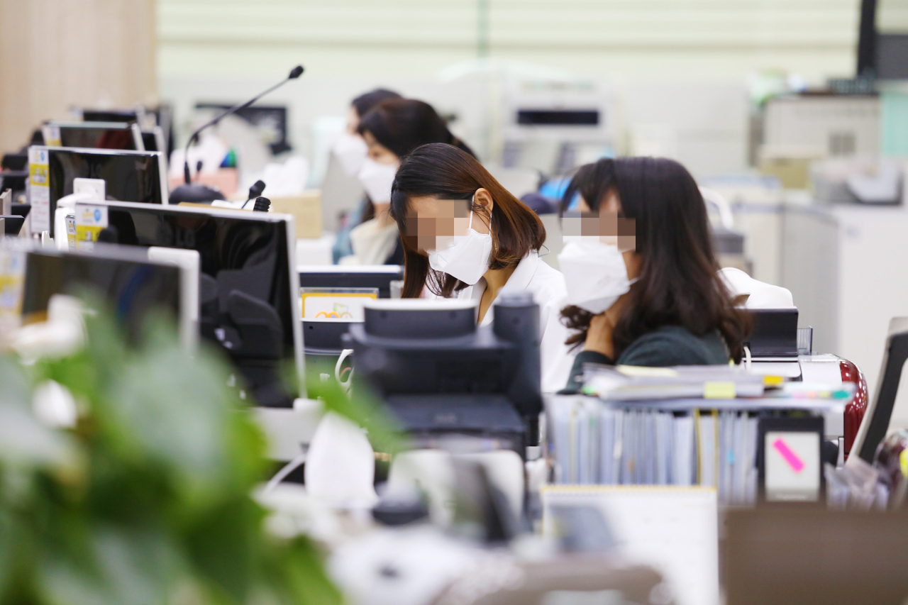 Employees at a KB Kookmin Bank branch in western Seoul wear facial masks to prevent the spread of coronavirus, in this photo taken Tuesday. (Yonhap)