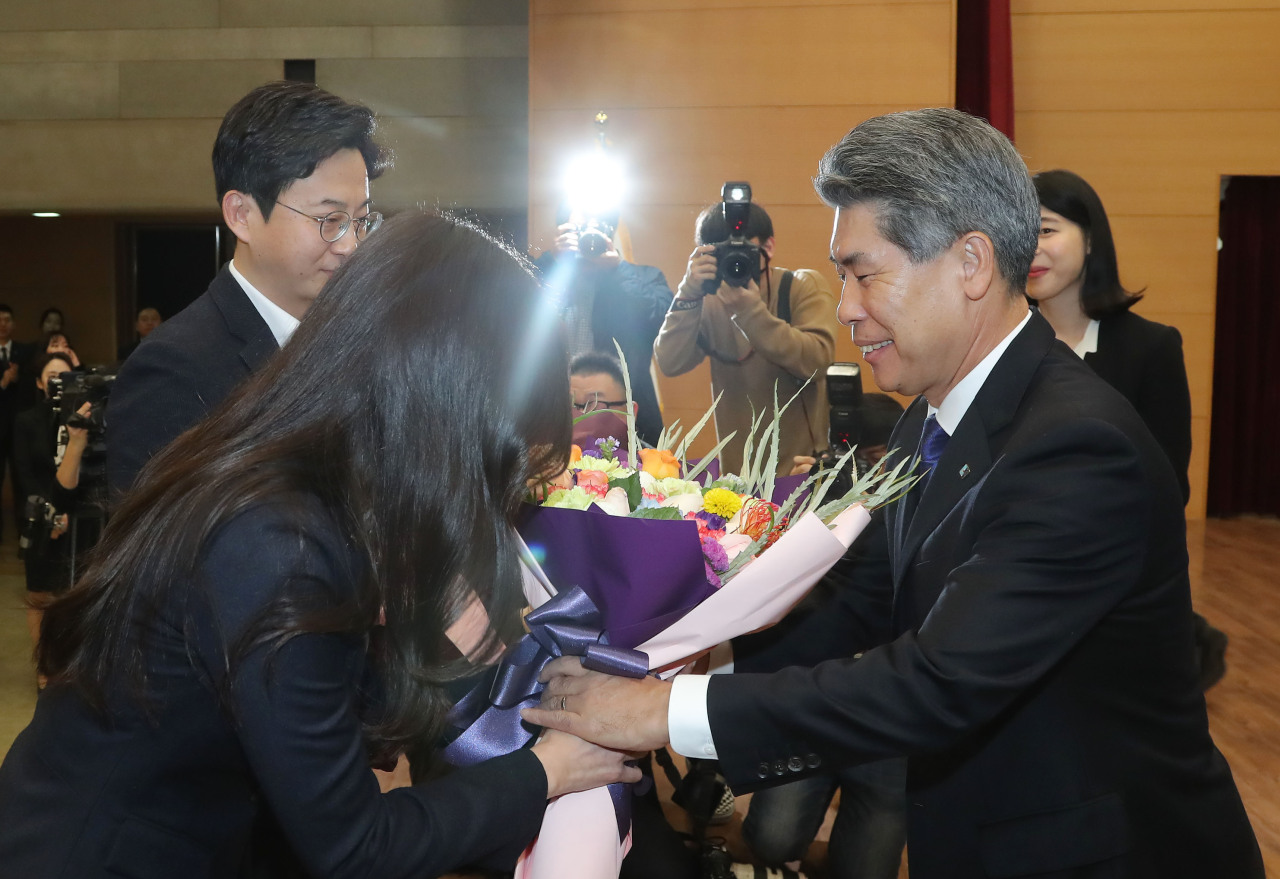 New IBK CEO Yoon Jong-won (right) receives a bouquet from a staff member at his inauguration ceremony, at the bank's headquarters in central Seoul on Wednesday. (Yonhap)