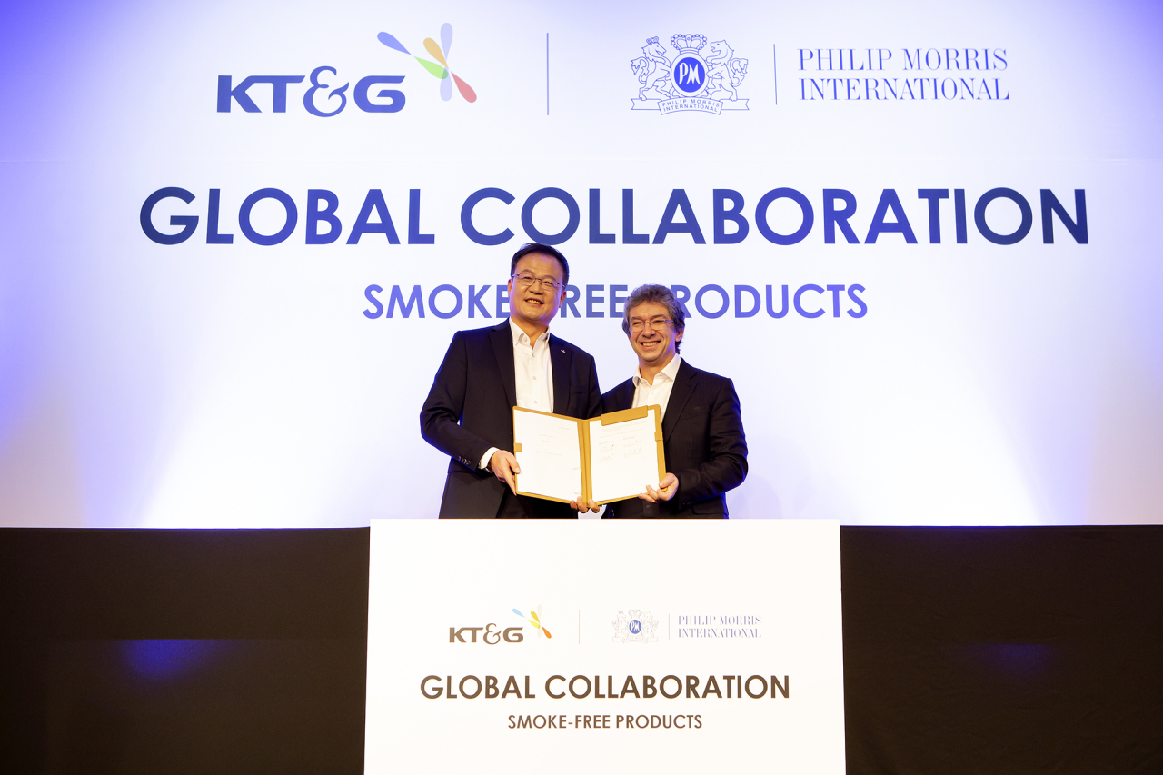 KT&G President Baek Bok-in (left) and PMI CEO Andre Calantzopoulos pose after they sign the supply contract for KT&G's heated e-cigarette brand lil, in Seoul on Wednesday. (KT&G)