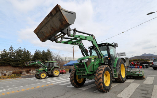 Local residents use tractors to block the road to a police training facility in Asan, South Chungcheong Province, Wednesday, to prevent the building from being used as a quarantine center. Hundreds of South Korean nationals are to be flown in on Thursday from Wuhan, China, the epicenter of a deadly virus outbreak. The Asan facility is one of two locations where they will stay for at least 14 days.(Yonhap)