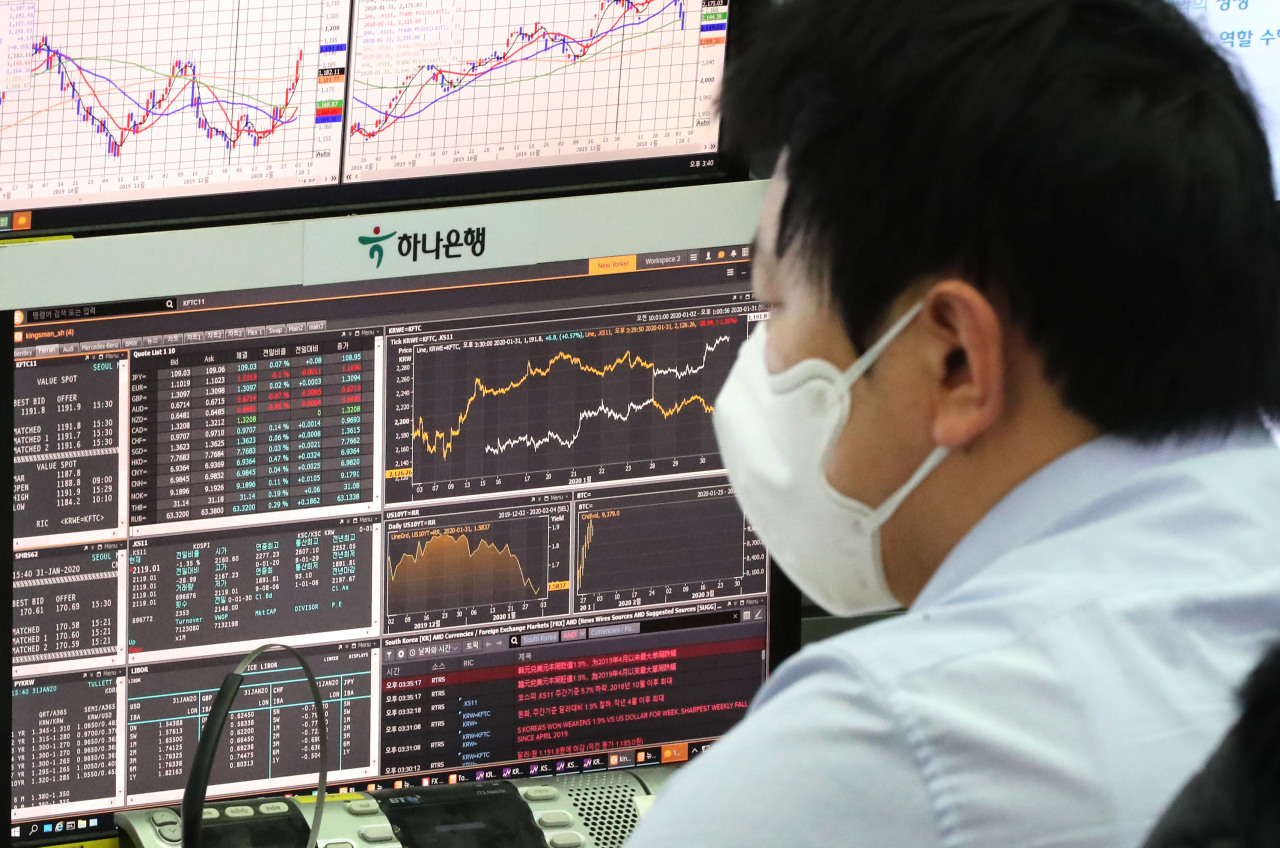 A trader wearing a mask monitors data at the foreign exchange dealing room of the Hana Bank headquarters in Seoul on Friday. (Yonhap)