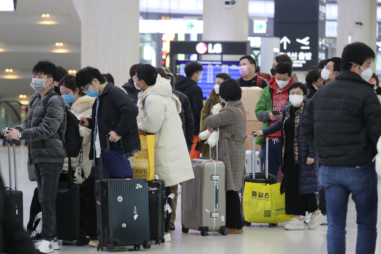 Passengers wait for a flight to Shanghai at Jeju International Airport on Monday. (Yonhap)