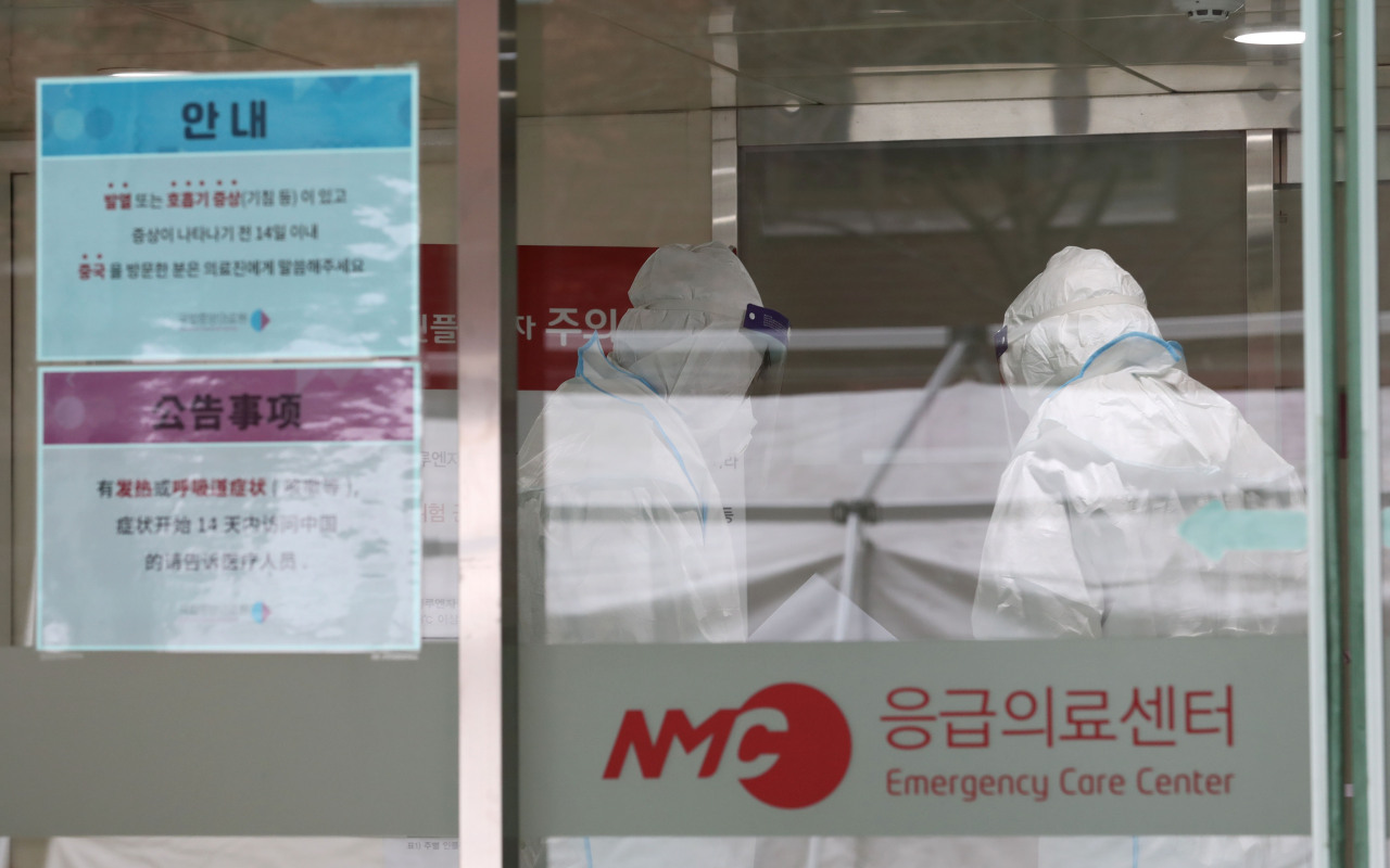 Medical staff at the National Medical Center in Seoul are photographed in full-body protective suits on Jan. 28. (Yonhap)