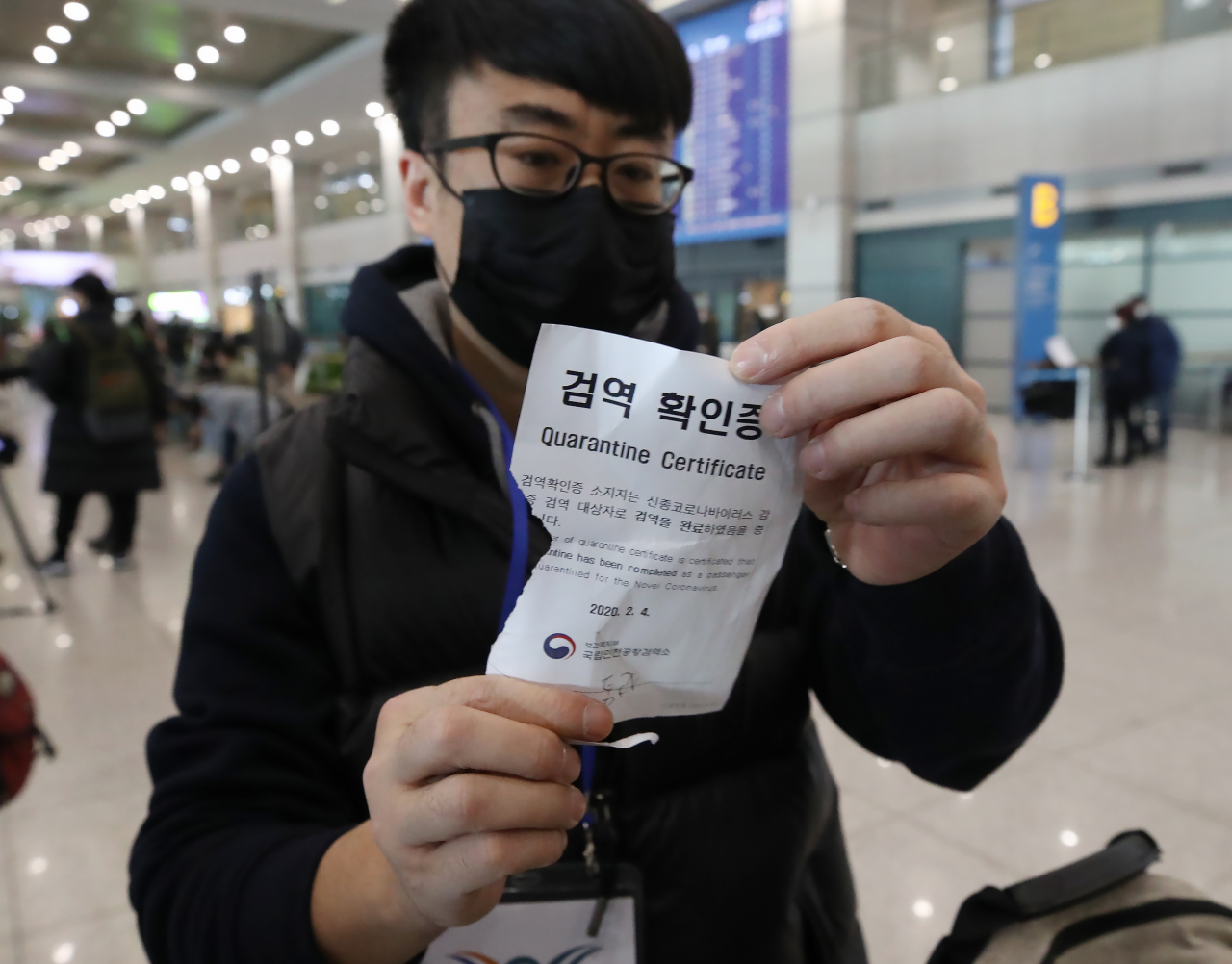A Chinese national shows a certificate stating the holder has been cleared by Korean quarantine authorities upon arrival at Incheon Airport on Tuesday. (Yonhap)