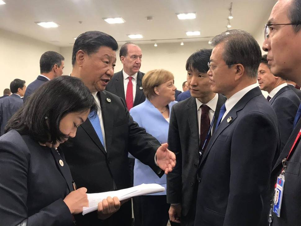 President Moon Jae-in (right) talks with his Chinese counterpart Xi Jinping during the G-20 Summit in Osaka, Japan in June 2019. The novel coronavirus outbreak is projected to deal a severe blow to South Korea's private consumption and exports in the first quarter this year. (Cheong Wa Dae)