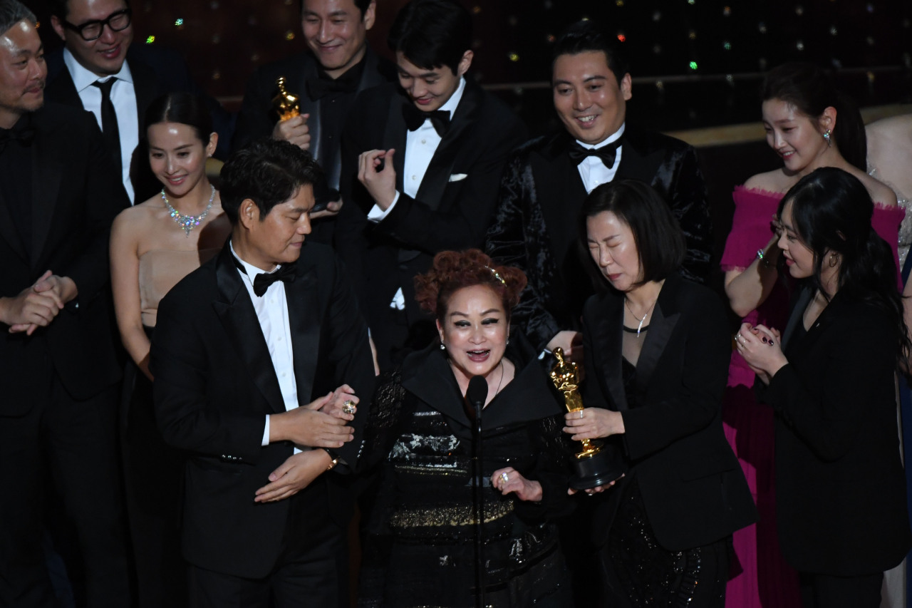 Lee Mi-kyung, vice chairwoman of CJ Group (center), alongside cast and crew, accept the award for Best Picture for