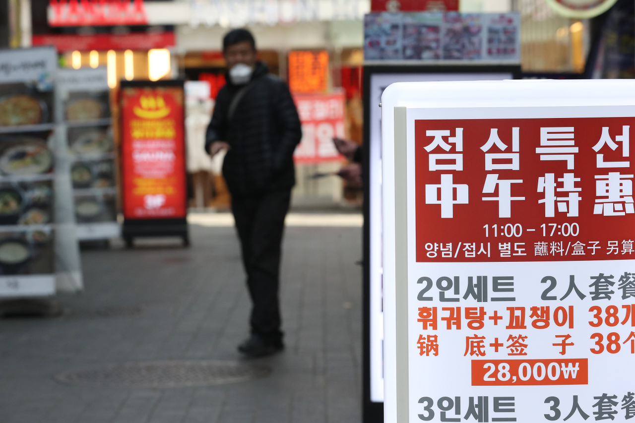 A person wearing a face mask looks at a menu on an empty street in Myeongdong. The popular shopping district in Seoul has been deserted in the wake of novel coronavirus outbreak. (Yonhap)