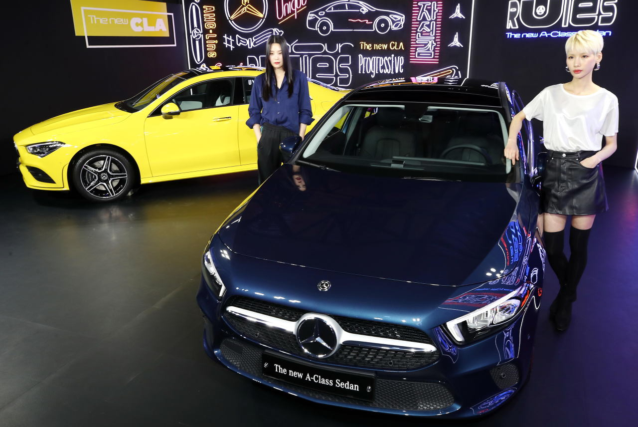 Models pose with Mercedes-Benz's new A-Class sedan (right) during the launching event held in Seoul on Tuesday. (Yonhap)