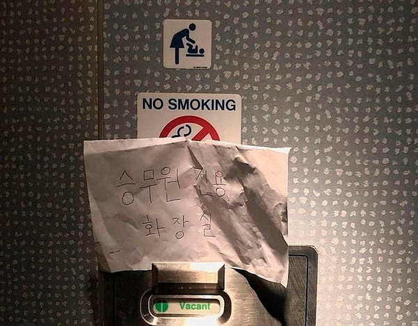 """A hand-written note that reads """"cabin crew exclusive restroom"""" is posted on the door of a restroom on KLM flight."""
