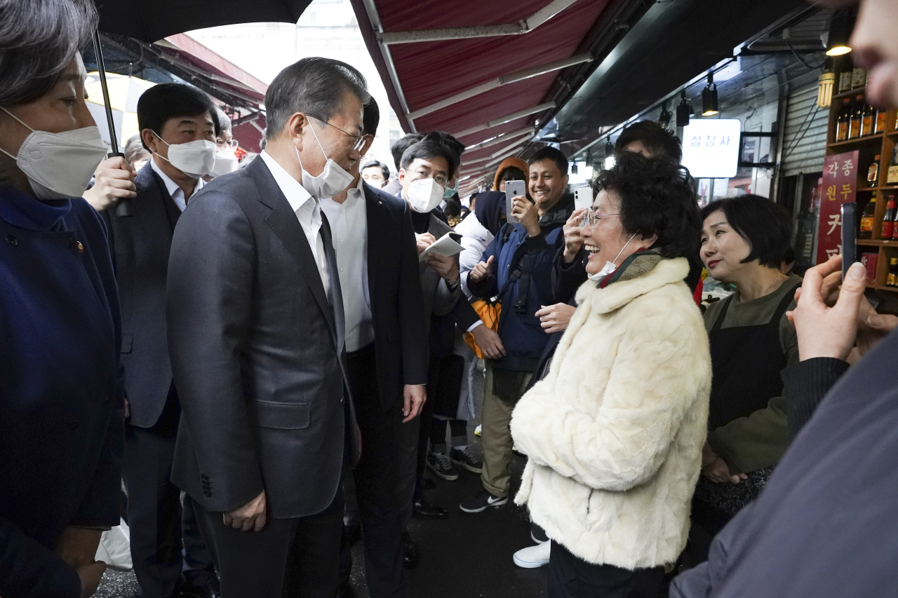 President Moon Jae-in has called on the public to overcome virus fears and carry on with everyday life during a visit to a traditional market last week. (Yonhap)