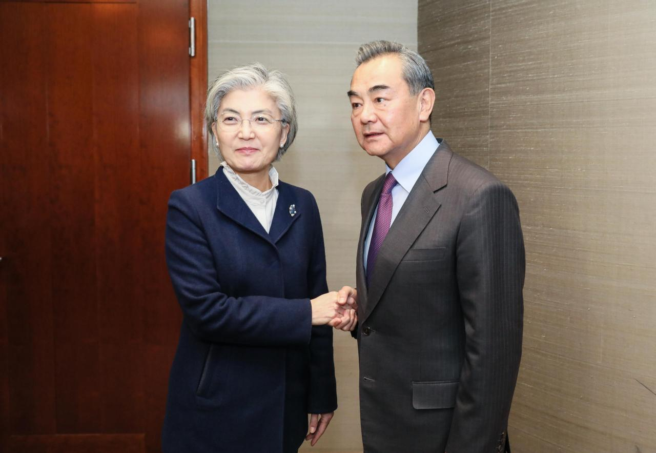 South Korean Foreign Minister Kang Kyung-wha (left) shakes hands with Chinese Foreign Minister Wang Yi during thir meeting on Saturday held on the sidelines of the annual Munich Security Conference. (Ministry of Foreign Affairs)