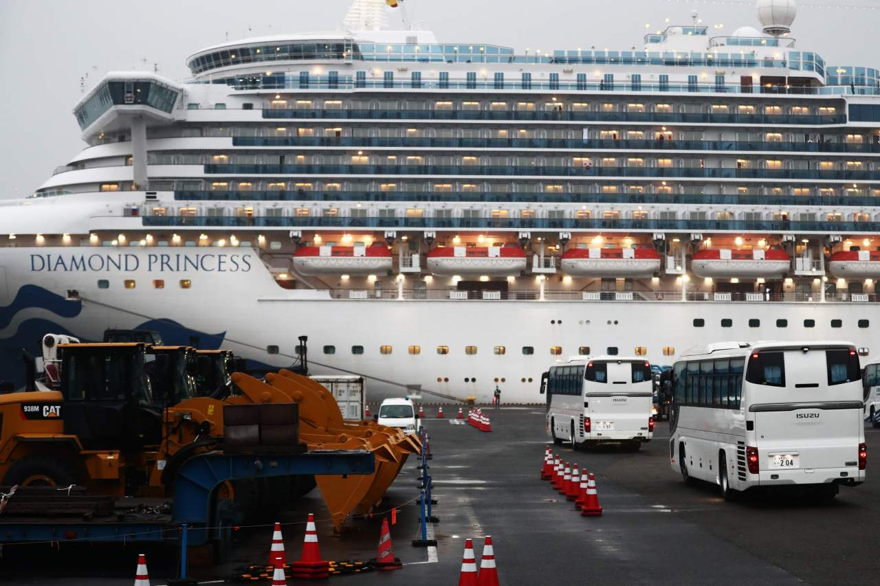 Two buses arrive next to the Diamond Princess cruise ship, with people quarantined onboard due to fears of the new coronavirus, at the Daikaku Pier Cruise Terminal in Yokohama port on Sunday. (Yonhap)