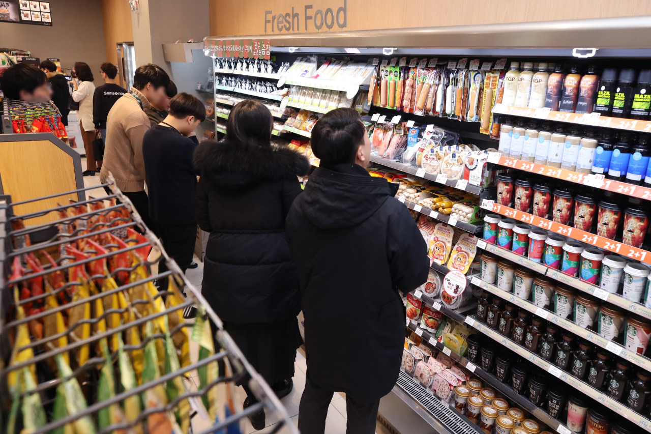 Shoppers browse items at a convenience store in Seoul on Monday. (Yonhap)