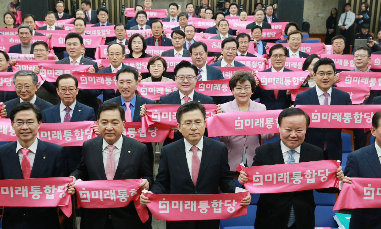 Chairman Hwang Kyo-han (center) and lawmakers of the new Party for Future Integration hold pink banners at the National Assembly in Seoul on Tuesday. Pink is the party's official color for the April elections. (Yonhap)