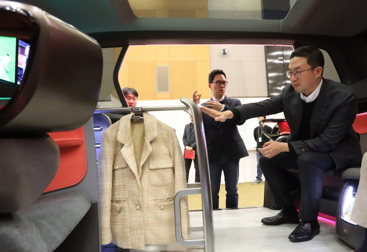 LG Group Chairman and Chief Executive Koo Kwang-mo (right)looks at the design of a clothing storage unit set up inside a connected car model at the company`s research and development campus in Seocho-gu, Seoul, Tuesday. (Yonhap)