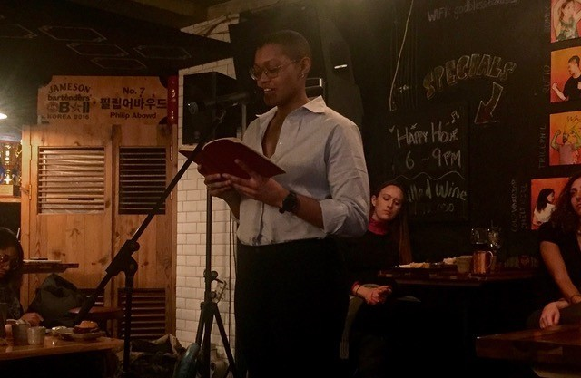 Erica Butler performs her poetry at Wordsmiths' February event. (Jack Ryan/The Korea Herald)