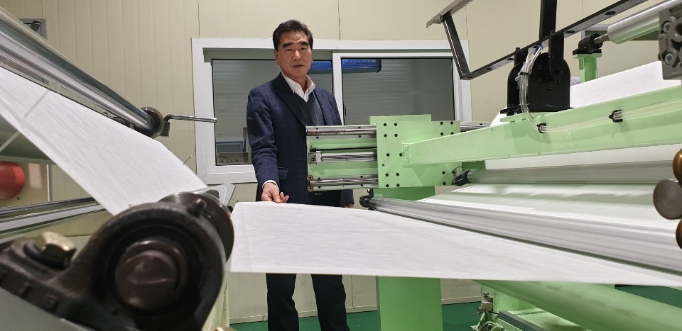Hwang Kyu-ik, founder and president of meltblown nonwoven fabric maker E&H, looks at a machine rolling out the material for face masks, at the firm's headquarters in Pocheon, Gyeonggi Province, Tuesday. (Kim Young-won/ The Korea Herald)