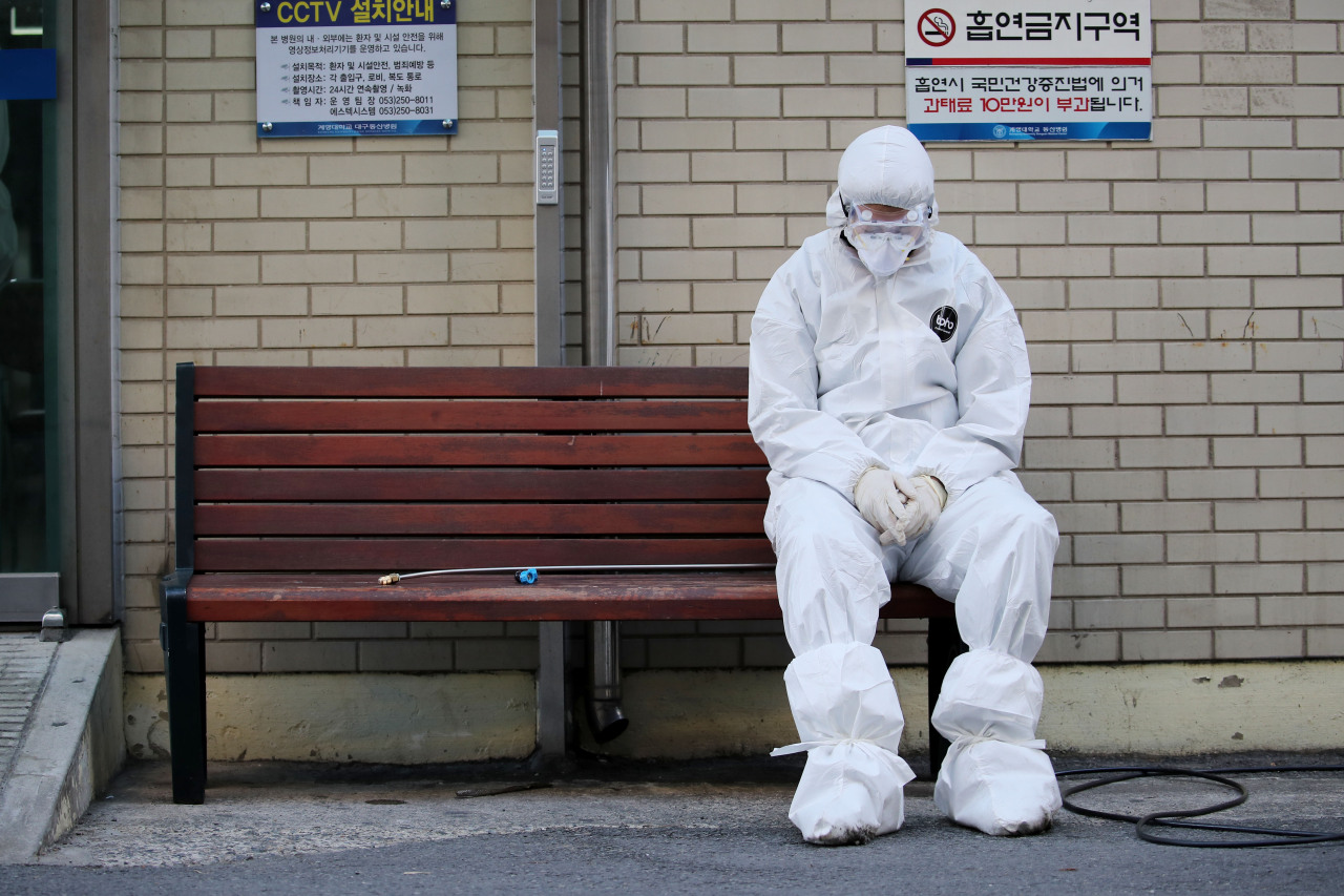 A health worker sits outside a hospital in Daegu on Sunday. (Yonhap)