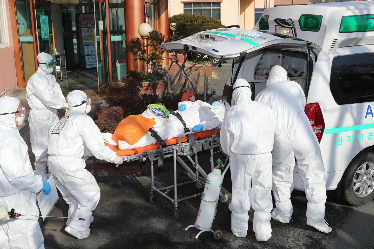 Medics transport a suspected patient via an ambulance on Friday. (Yonhap)