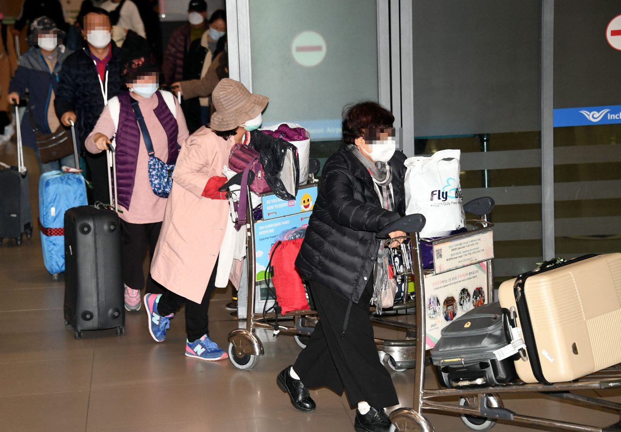 A group of Korean tourists, flown back home from Israel on a chartered flight arranged by the Israeli government, are seen at the Incheon Airport, west of Seoul, Tuesday morning. (Yonhap)