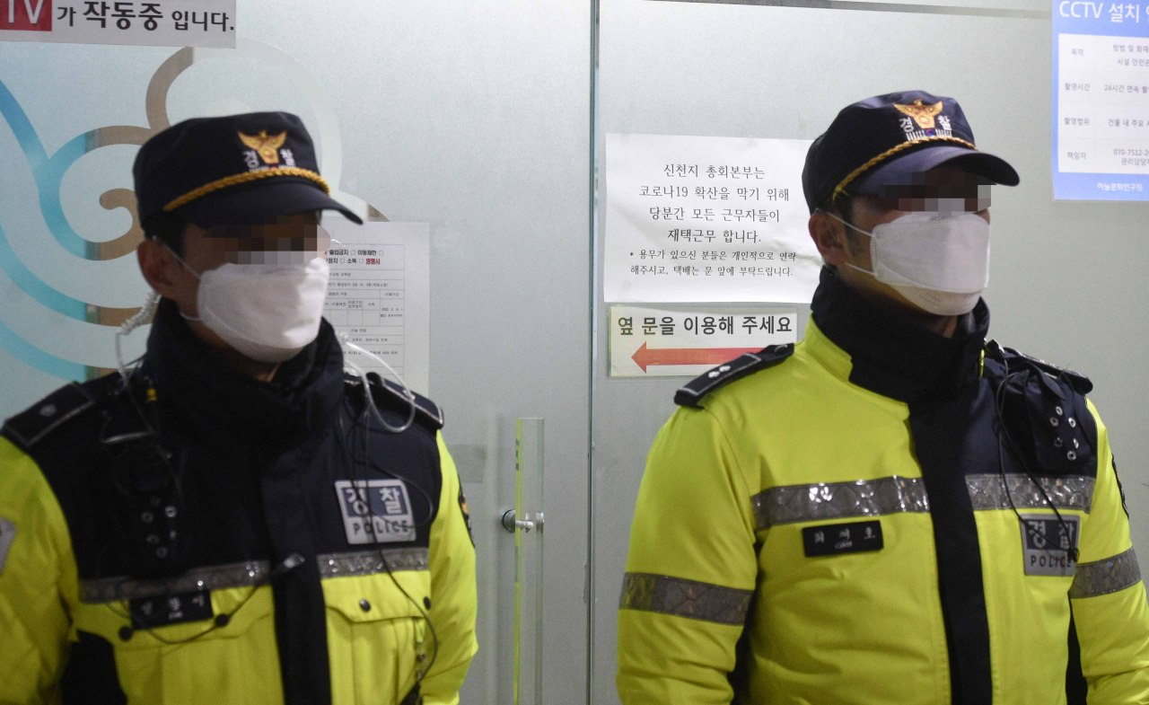 Police officers guard the entrace to an office used by the Shincheonji Church of Jesus in Gwacheon, just south of Seoul, Tuesday. (Yonhap)