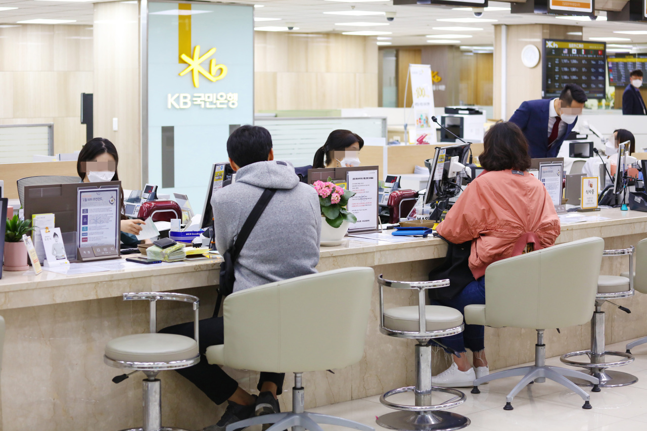 In this photo taken on Jan. 28, KB Kookmin Bank employees wear face masks in front of customers to prevent the spread of coronavirus. (Yonhap)