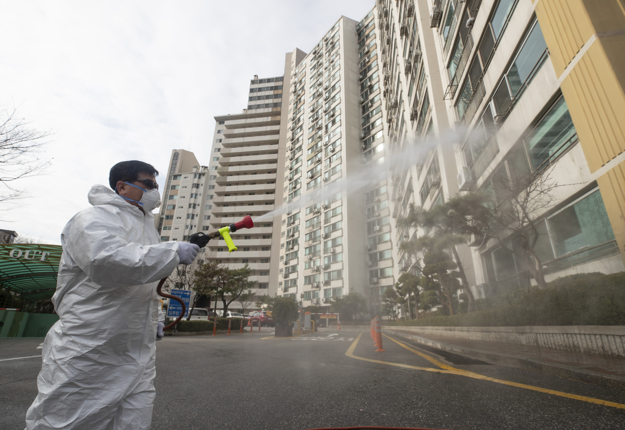 Gangdong Health Center officials fumigate the entrance to an apartment in a neighborhood near Myungsung Church, where a pastor and other church members are quarantined, in Gangdong, Seoul, Wednesday. (Yonhap)