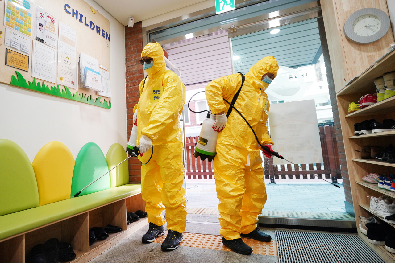 Local volunteers are seen fumigating the entrance to a kindergarten in Dongdaemun, Seoul, Tuesday. (Yonhap)