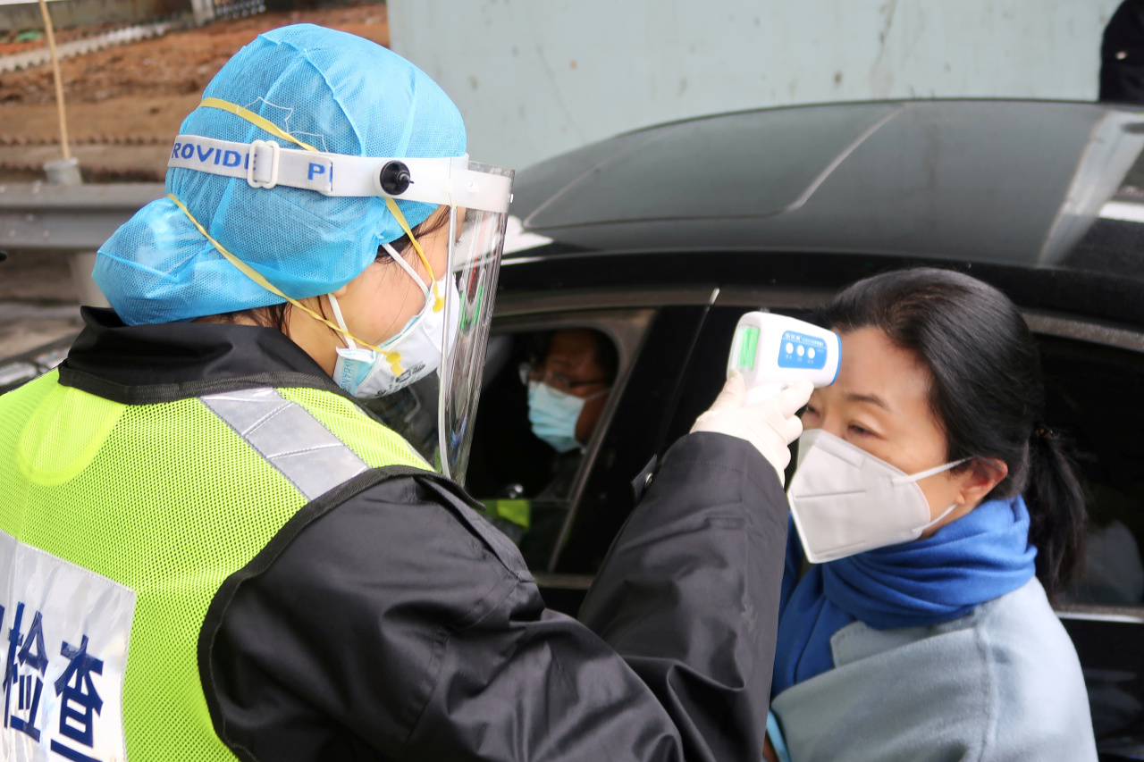 A security officer checks the temperature of a passenger following the outbreak of COVID-19 at an expressway toll station in Xianning, a city bordering Wuhan to the north, Hubei province, China on the eve of the Chinese Lunar New Year celebrations (Yonhap)