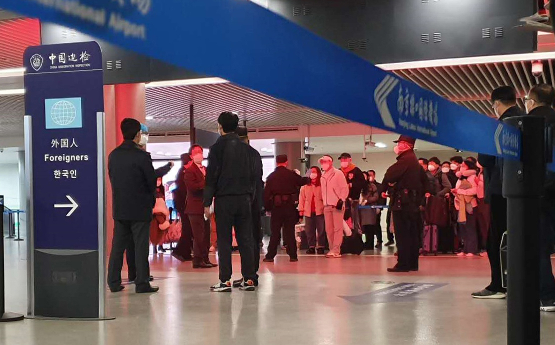 Koreans are separately screened by Chinese health authorities at an airport in Nanjing, Jiangsu province, on Tuesday. (Yonhap)