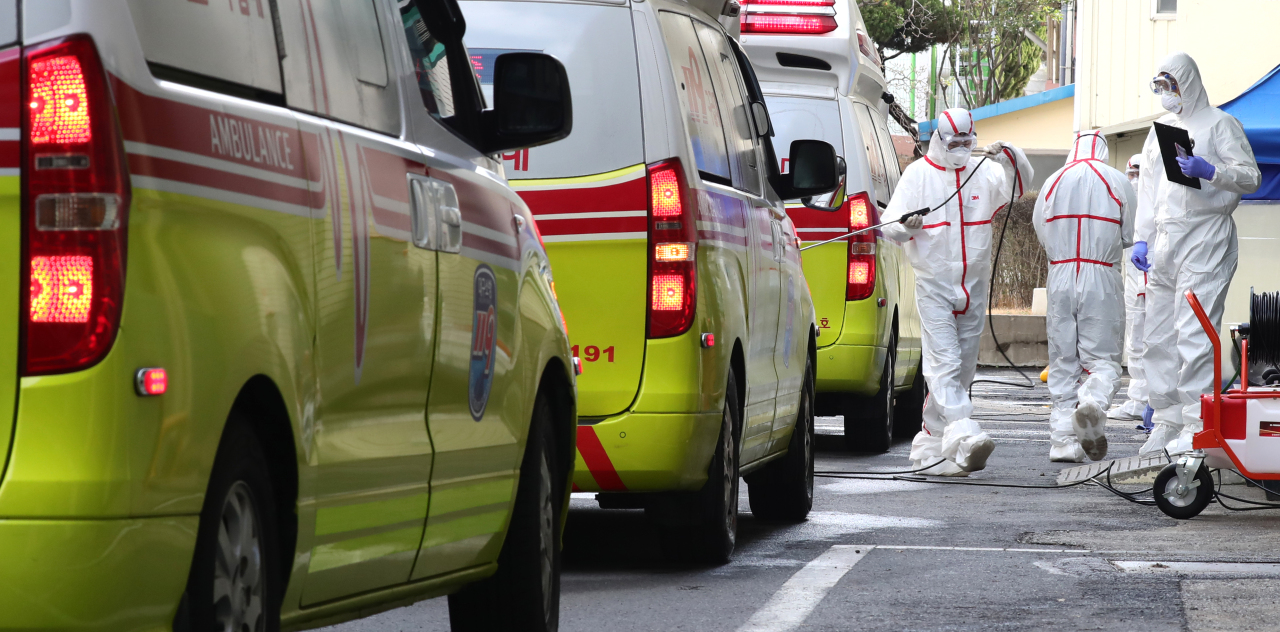 Health workers in protective suits stand next to a line of ambulancesoutside a hospital in central Daegu. (Yonhap)