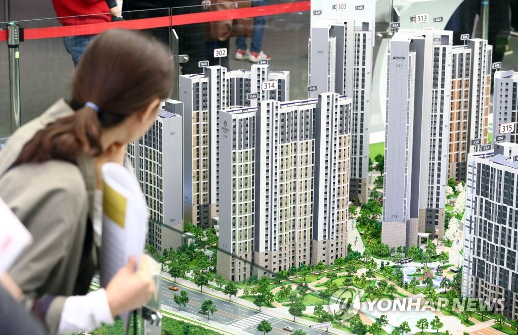 A visitor to a showroom for a new apartment complex looks at miniature apartments. (Yonhap)