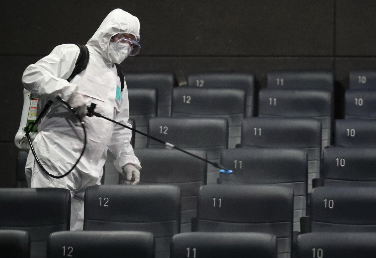 A health official in a protective suit helps disinfect a movie theater in Lotte Cinema near Konkuk University in Gwangjin-gu, eastern Seoul. (Yonhap)
