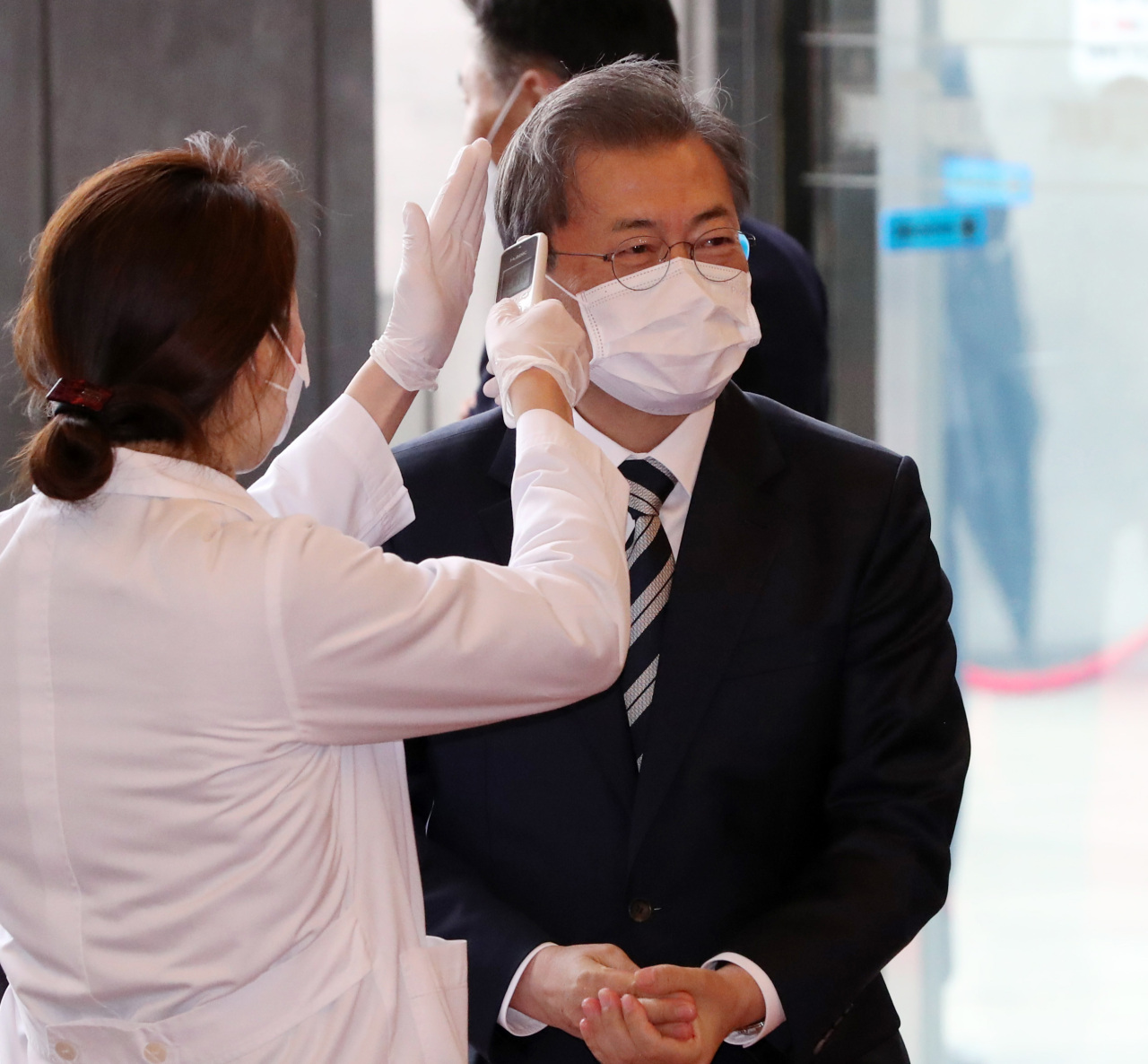 Face mask-donning President Moon Jae-in has his temperature checked before entering the National Assembly building in Yeouido, central Seoul, on Friday. (Yonhap)