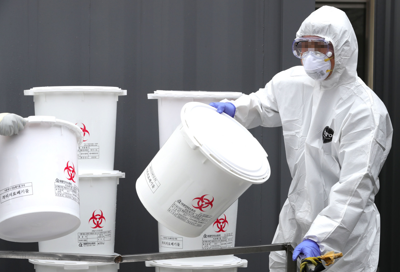 A medical staff at Dongsan Hospital in coronavirus-stricken Daegu moves medical waste on Saturday. (Yonhap)