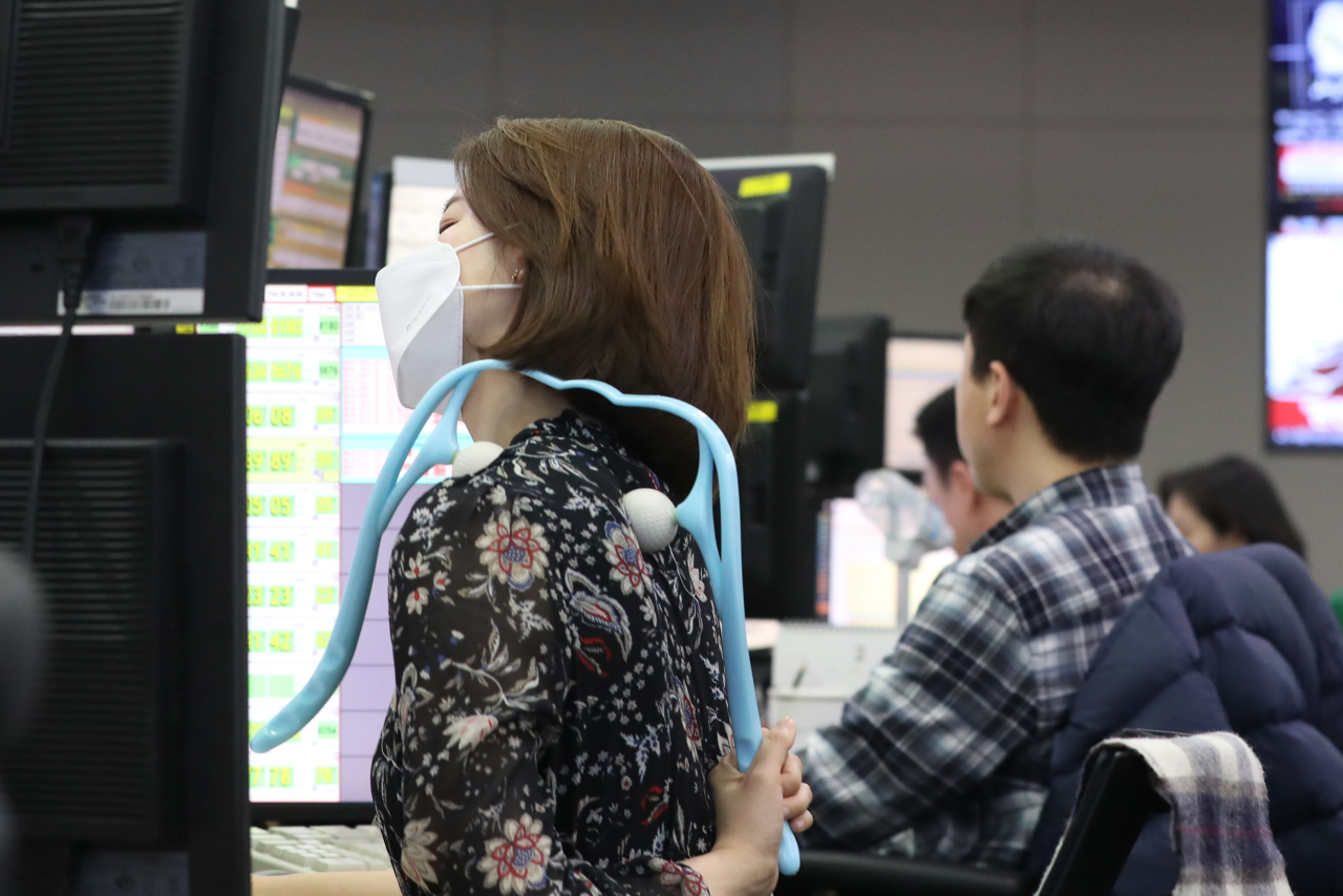 A masked employee at the dealing room of KEB Hana Bank in Seoul uses an acupressure rod on Friday, when the Kospi closed below 2,000 points. (Yonhap)