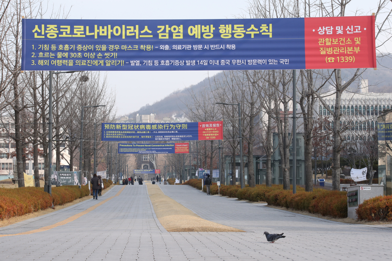 Yonsei University's campus in Seoul is seen empty with a COVID-19 precaution banner on display Monday, the day when new school year was supposed to commence. Due to coronavirus concerns, the university has postponed the new semester by two weeks, along with other schools here. (Yonhap)