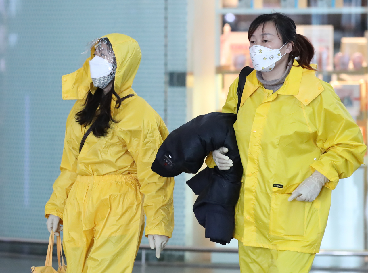 Chinese people wearing masks and yellow raincoats at Incheon International Airport Terminal 1, on Tuesday. (Yonhap)