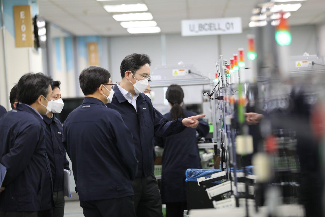 Samsung Vice Chairman Lee Jae-yong checks the manufacturing process of smartphones at the company's plant in Gumi, North Gyeongsang Province, on Tuesday. (Samsung Electronics)