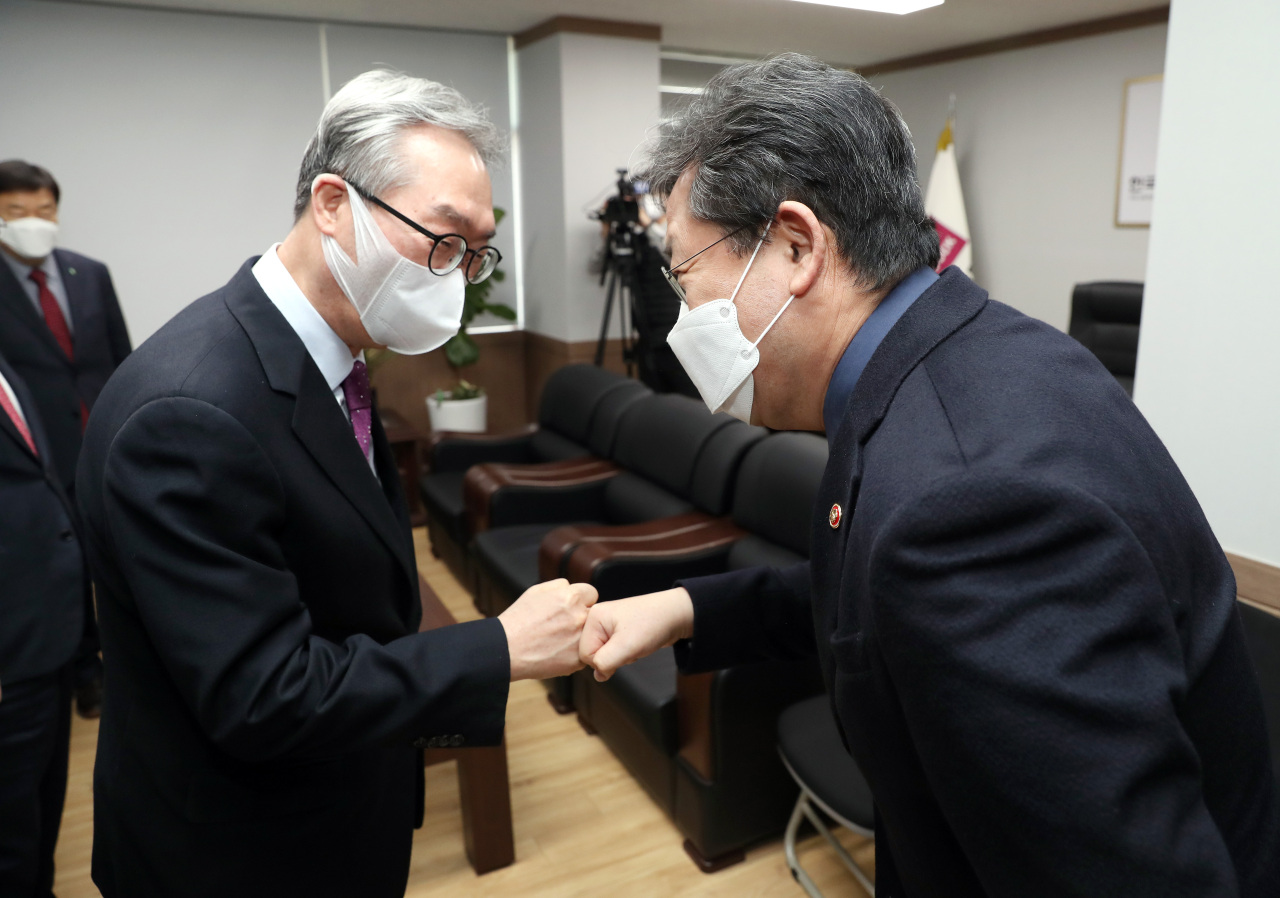 Head of United Christian Churches of Korea Kim Tae-young (left) and Culture Minister Park Yang-woo fist bump at their meeting Tuesday at the United Christian Churches of Korea office in Seoul. (Ministry of Culture, Sports and Tourism)