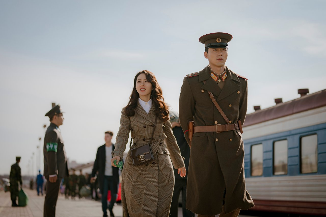 """South Korean Yoon Se-ri, played by Son Ye-jin (left), and North Korean military official Ri Jung-hyuk, played by Hyun Bin, arrive in Pyongyang in a scene from """"Crash Landing on You."""" (Studio Dragon)"""
