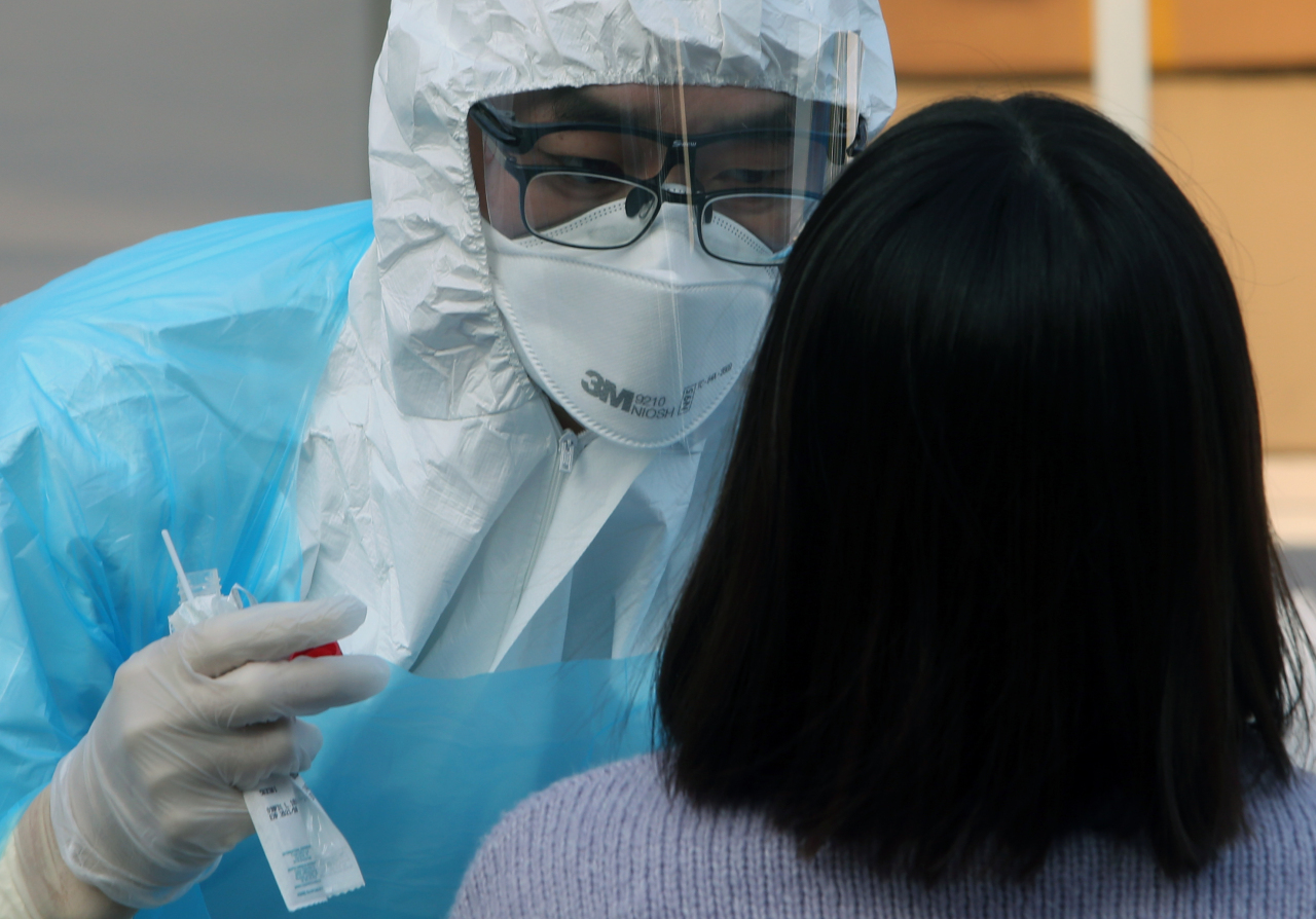 A staff at a hospital in Gangneung, Gangwon Province collects samples for testing on Saturday. Yonhap